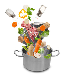 Fresh vegetables falling into stainless steel pot