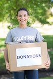 Pretty volunteer holding a donation box in park