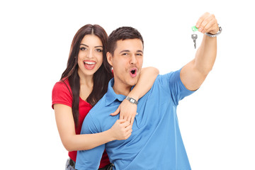 Joyful couple holding a key and gesturing happiness