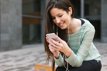 Young beautiful woman listening to music with phone in outdoors.