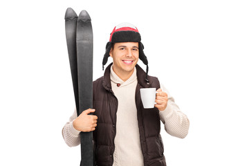 Young man holding skis and drinking hot tea