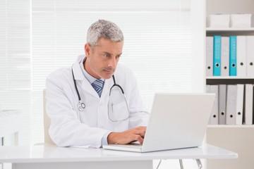 Serious doctor using laptop