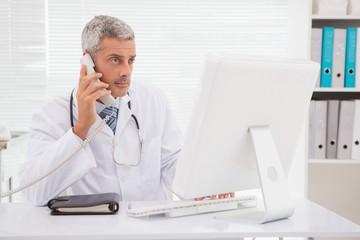 Doctor phoning and using computer