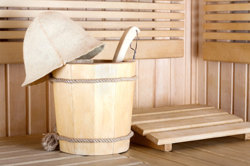 Traditional wooden sauna for relaxation with bucket of water