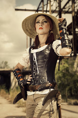 Young steampunk woman in leather corset and vietnam hat  standin