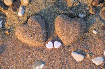 Two sand heart shape in the sand by the sea