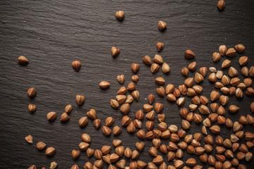 Buckwheat is sprinkled on black slate stone