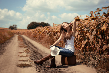 Young woman with retro suitcase traveling in countryside, summer