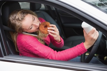 Young woman having coffee and doughnut