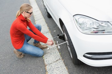 Young woman replacing tire