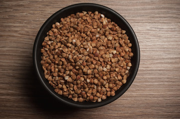 Buckwheat in black bowl on wooden background. Closeup.