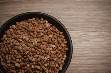 Buckwheat in bowl on wooden background. Closeup.