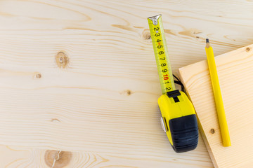 Measuring tape and a pencil on a wooden background