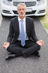 Businessman meditating after his car broken down