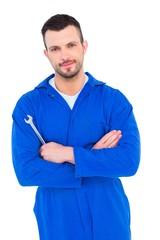 Smiling male mechanic holding spanner