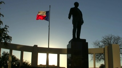 Texas Flag And Statue At Sunset