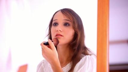 Beautiful young girl paints lips powder preens near the mirror