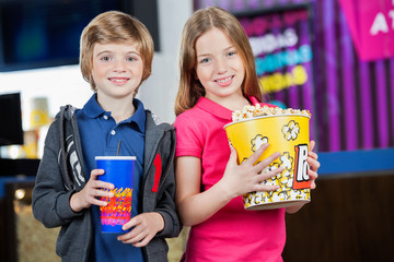 Siblings Holding Popcorn And Drink At Cinema