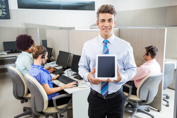 Smiling Manager Holding Tablet Computer At Call Center