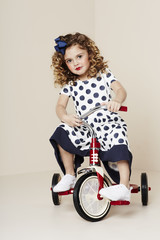 Girl in spotty dress on tricycle