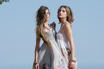 Outdoor fashion shot of two young womens in dress