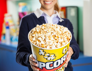 Worker Offering Popcorn Bucket At Cinema Concession Stand