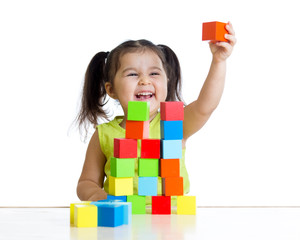 child plays with building blocks and shows red cube