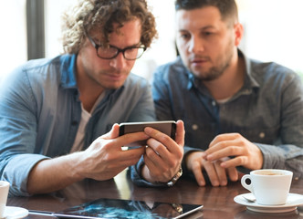 Casual guys in a Cafe looking at mobile phone
