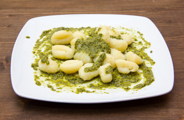 Gnocchi with basil pesto on wooden table