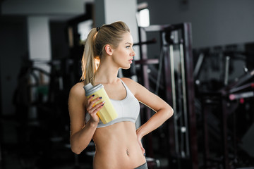 Beautiful athletic girl  poses in the gym with a yellow shaker.