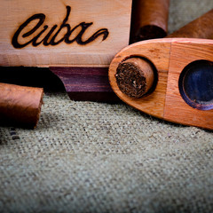 Cuban cigars with cutter on a hessian background