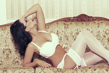 Sexy woman in white underwear posing on sofa