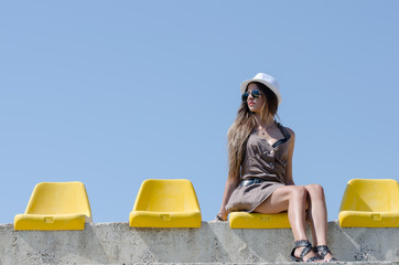 Woman portrait with hat sitting on yellow stadium chair