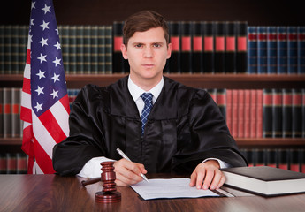 Male Judge Sitting In Courtroom