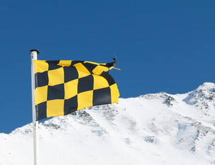 Yellow and black avalanche risk warning flag flying in the mount