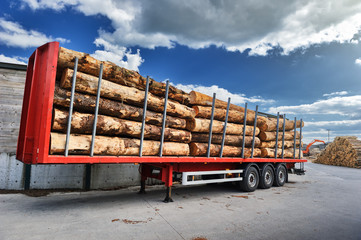 Trucks charged with wood logs waiting for delivery