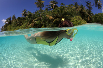 Female snorkeler diving in front of tropical island