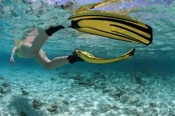Female snorkeler diving in beautiful blue lagoon