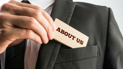 Businessman showing a wooden card reading - About us