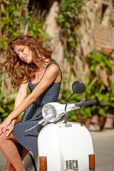 beautiful italian woman sitting on a italian scooter.