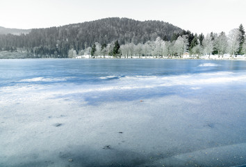 Landscape of frozen Longemer lake in the Vosges Mountain, France