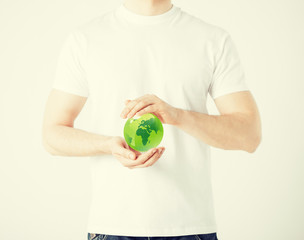 man hands holding green sphere globe