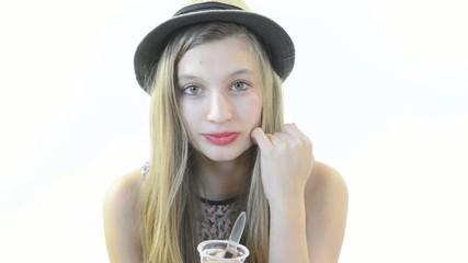 a teenage girl eats a chocolate yogurt
