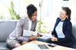 Image of two friendly businesswomen sitting and discussing