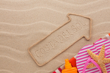 Costa del Sol pointer and beach accessories lying on the sand