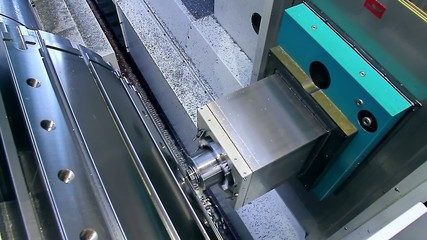 An industrial machine is drilling metal