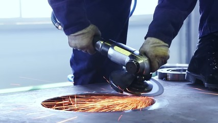 Man is working with a grinding machine at an industrial factory