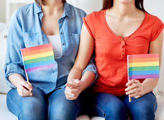 close up of lesbian couple with rainbow flags