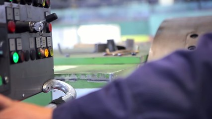 A machine operator turns on an industrial machine