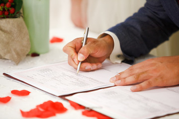 groom signs marriage certificate with a pen